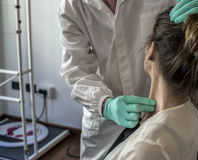 Cervical and headache. Medical doctor visits a young girl suffering cervical and headache Royalty Free Stock Photos