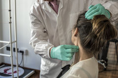 Cervical and headache. Medical doctor visits a young girl suffering cervical and headache Royalty Free Stock Photography
