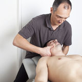 Cervical manipulation. Physical therapist with patient applying cervical manipulation Royalty Free Stock Photo