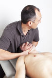 Cervical manipulation. Chiropractor applying cervical manipulation on white background Royalty Free Stock Image