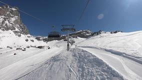 Cervinia, Italy. Skiers are moving to the top of the mountain with a chairlift. Skier point of view. Camera on helmet. Italian Alps in winter at Breuil stock video footage