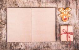 Cervos do pão-de-espécie, livro aberto e presente Conceito do Natal Imagem de Stock