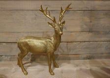 Cervos dourados na frente de uma parede de madeira Decoração do Natal foto de stock royalty free