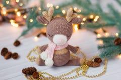 Cervos feitos malha do bebê no fundo do Natal com luzes de Natal, cones do pinho e árvore de Natal foto de stock royalty free
