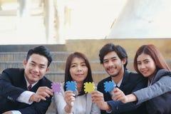 Ces jeunes hommes d'affaires asiatiques tiennent des puzzles denteux de prise pour chacun photo libre de droits