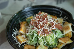 Cesar salad in black bowl. On table Royalty Free Stock Photo