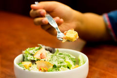 Cesar salad. Hand of girl holding a spoon of cesar salad over cesar salad bowl Stock Images