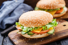 Cesare burger on wooden board. Cesare burger with grilled chicken breast, cucumber, tomato, cheese and fresh salad leaf Royalty Free Stock Image