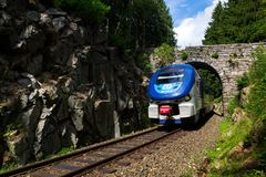 Ceske drahy CD railway carrier company train passes under romantic stone bridge in beautiful forest in Ore Mountains royalty free stock images