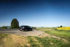 Ceske Stredohori, Tjeckien - Maj 19, 2017: den svarta ställningen för bilOpel Astra H vid vägen between våldtar fält under våreft Arkivfoton