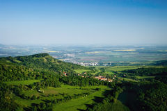 Ceske Stredohori tourist area with hill Kamyk and Litomerice city on horizont and Kundratice village in foreground in spring eveni Stock Image