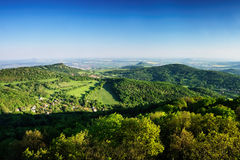 Ceske Stredohori tourist area with hill Kamyk and Litomerice city on horizont and Kundratice village in foreground in spring eveni Royalty Free Stock Image