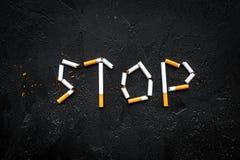 Cessez le fumage Exprimez les cigarettes rayées par arrêt sur l'espace noir de copie de vue supérieure de fond image stock