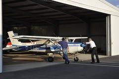 Cessna 152 die terug in de Hanger wordt geduwd Royalty-vrije Stock Foto's