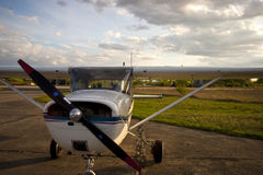 Cessna airplane. Cessna: a small airplane stands on the airfield at sunset, with clouds in the background Stock Photos