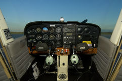 Cessna Cockpit With Headsets. Inside a cessna facing the cockpit and headsets hanging off the steering.  All logos and registrations removed - only generic Stock Photo
