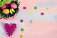 Cesta colorida brilhante do feltro com ovos pintados e da galinha em um fundo cor-de-rosa-azul Feito a m?o do feltro Cumprimento  foto de stock royalty free