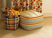 Cesta colorida con los juguetes, la cortina y Seat de la felpa Fotos de archivo