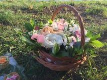 Cesta com as flores frescas na grama verde Imagem de Stock Royalty Free