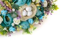 Cesta com as flores para comemorar a Páscoa em um fundo branco Fotografia de Stock
