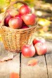 Cesta com as maçãs vermelhas na tabela de madeira Imagem de Stock Royalty Free