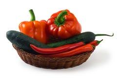 Cesta com as pimentas vermelhas e o pepino isolados no branco Foto de Stock