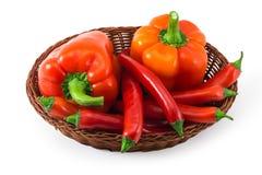 Cesta com as pimentas vermelhas isoladas no branco Foto de Stock