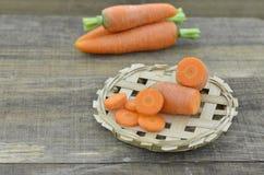 Cesta com cenouras, fatias e salsa frescas em de madeira Fotografia de Stock Royalty Free
