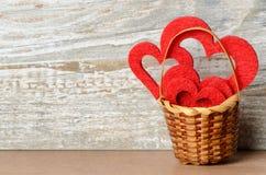 Cesta com corações vermelhos contra o fundo de madeira como um Valentine Foto de Stock
