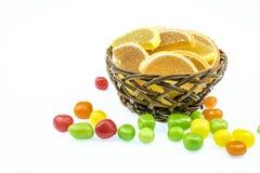 Cesta com fatias alaranjadas e os doces redondos de cores diferentes Fotos de Stock