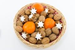 Cesta com nozes, tangerinas e estrelas da canela Fotografia de Stock Royalty Free