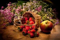 Cesta con Apple, la fresa y las flores Fotos de archivo