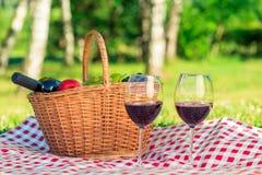 Cesta con el vino rojo y frutas y dos vidrios de vino en una etiqueta Imagen de archivo
