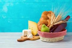 Cesta con la botella, el pan y el queso de vino en la tabla de madera Día de fiesta judío Shavuot Fotografía de archivo libre de regalías