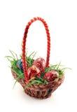 Cesta con la hierba y los huevos de Pascua coloreados Imágenes de archivo libres de regalías