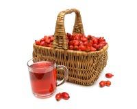 Cesta con las bayas de color de rosa salvaje y una bebida en una taza de cristal en a Fotografía de archivo