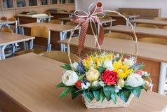 Cesta con las flores en el escritorio en sala de clase imágenes de archivo libres de regalías
