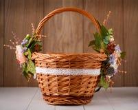 Cesta con las flores para celebrar Pascua en un fondo de madera Fotos de archivo