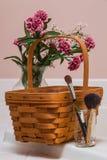Cesta con las flores y los cepillos del maquillaje fotografía de archivo libre de regalías
