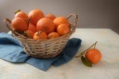 Cesta con las frutas y las clementinas anaranjadas frescas con las hojas en a Fotografía de archivo libre de regalías
