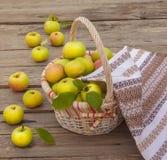 Cesta con las manzanas en un fondo de madera Imagen de archivo