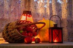 Cesta con las manzanas, una lámpara vieja de la linterna amarilla grande de la calabaza - todavía vida en el día de la acción de  Fotos de archivo