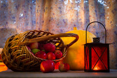 Cesta con las manzanas, una lámpara vieja de la linterna amarilla grande de la calabaza - todavía vida en el día de la acción de  Fotos de archivo libres de regalías