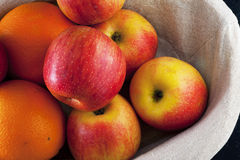 Cesta con las manzanas y las naranjas en un fondo azul Imagen de archivo libre de regalías