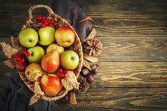 Cesta con las manzanas y las peras frescas en una tabla de madera Fondo del otoño Imagen de archivo libre de regalías