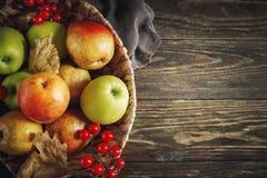 Cesta con las manzanas y las peras frescas en una tabla de madera Fondo del otoño Imagenes de archivo