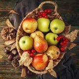 Cesta con las manzanas y las peras frescas en una tabla de madera Fondo del otoño Fotografía de archivo
