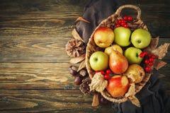 Cesta con las manzanas y las peras frescas en una tabla de madera Fondo del otoño Fotos de archivo libres de regalías