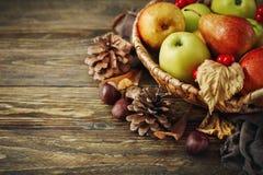 Cesta con las manzanas y las peras frescas en una tabla de madera Fondo del otoño Imagen de archivo