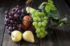 Cesta con las nectarinas, los melocotones, la uva y las peras Fotos de archivo libres de regalías